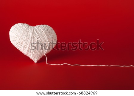White heart made of wool on a red background. Valentine's Day. - stock photo