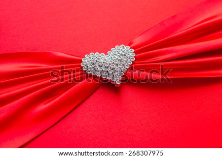 White heart on a background of red cloth. - stock photo