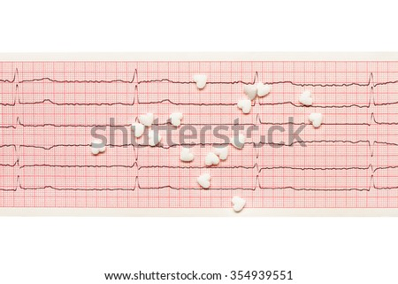 White heart shape tablets on paper ECG results isolated on white background. Clipping path included.