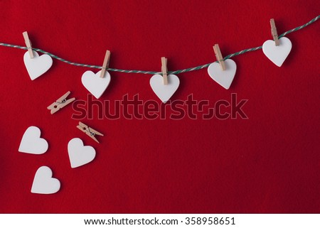 white hearts with clothespins hanging on clothesline over red background - stock photo