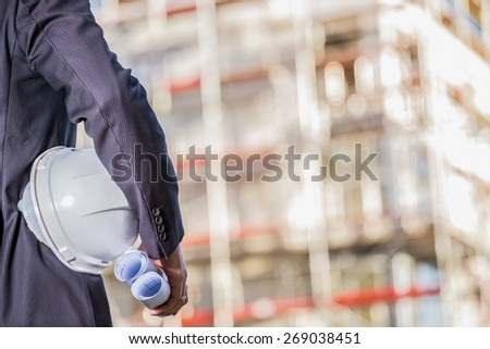 White helmet and blueprints  in hands of inspector entering construction site - stock photo