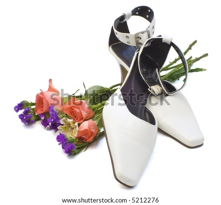 White high-heeled shoes with a bouquet of flowers on white background. - stock photo