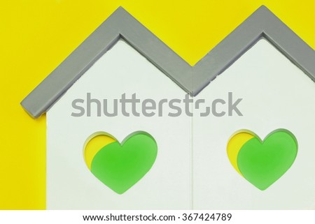White Home Wooden Shape With Two Yellow Green Heart Shape Window Isolated Background,Love Concept - stock photo