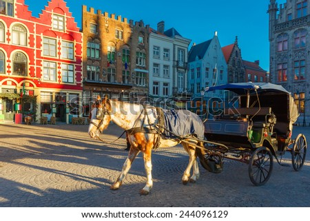 White horse hitched to a four wheel horse carriage waiting for tourists on Grote Markt square of Brugge Christmas, Belgium. - stock photo