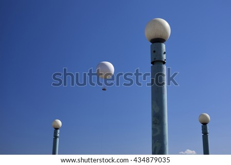 White hot air balloon between white ball street lamps against blue sky. Looks like a lamp has escaped a lamppost.  - stock photo