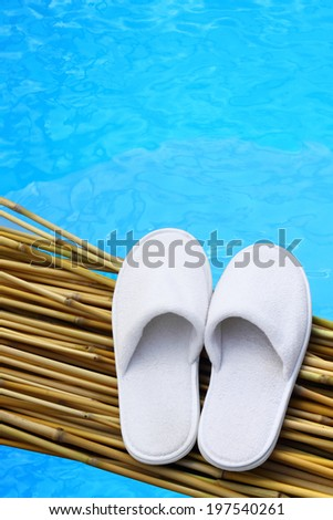 White hotel / home/ spa / wellness slippers on bamboo desk with swimming pool background with space for text - summer time - stock photo