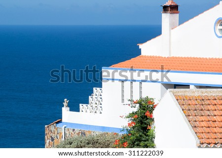 White house against deep blue sea along the beach in the coastline in natural park costa Vicentina, the southwest coast of Portugal, early in the morning - stock photo