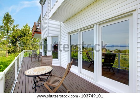 White house balcony deck with furniture and large doors. - stock photo