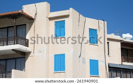 White house with blue shutters and wooden balcony. - stock photo