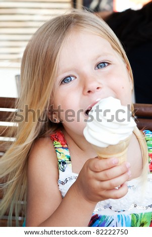 White ice cream in hand of beautiful little blonde girl - stock photo