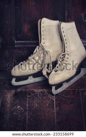 White ice skates on rustic wooden background - stock photo