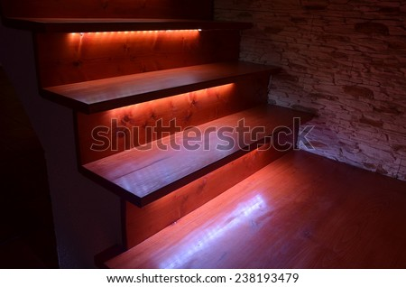 White illuminated wooden stairs and rough stone wall - stock photo