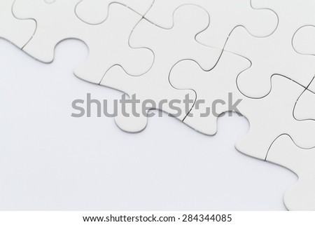 White incomplete jigsaw puzzle - stock photo