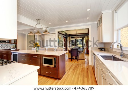 White interior of kitchen room with large kitchen island, modern pendant lights and storage combination. With dining room in the background. Northwest, USA