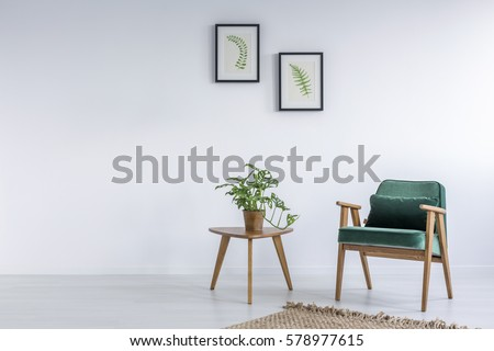 White interior with kale green chair, rug and small table