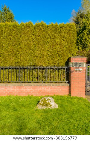 White iron fence with trimmed bush and green lawn. - stock photo
