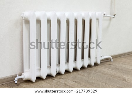 White iron radiator central heating in room - stock photo