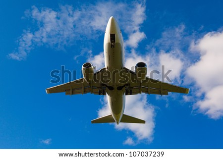 white jet passenger aircraft with gear against blue sky