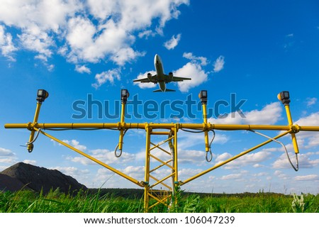 white jet passenger aircraft with the gear against the blue sky and landing lights and green grass, view from below - stock photo