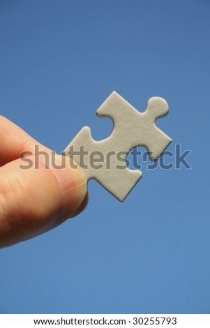 White jigsaw in human fingers on a blue sky background - Conceptual picture - stock photo