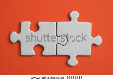 White jigsaw pieces on orange paper background - stock photo