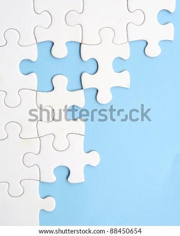 White jigsaw puzzle on blue background - stock photo
