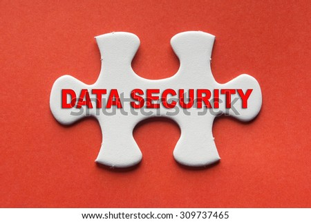 White jigsaw puzzle with a written word data security on a red background. - stock photo