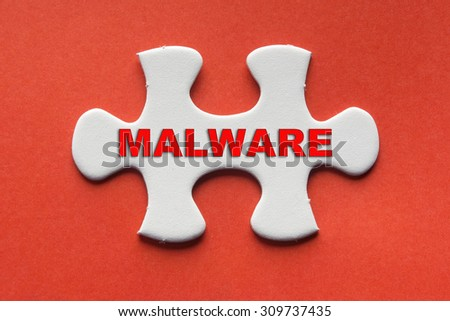 White jigsaw puzzle with a written word malware on a red background. - stock photo