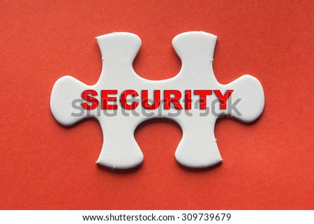 White jigsaw puzzle with a written word security on a red background. - stock photo
