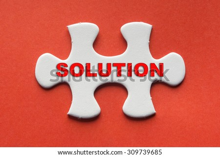 White jigsaw puzzle with a written word solution on a red background. - stock photo