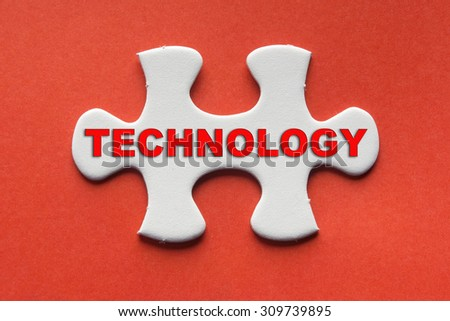 White jigsaw puzzle with a written word technology on a red background. - stock photo