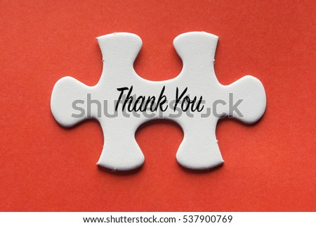 White jigsaw puzzle with a written word Thank You on a red background.