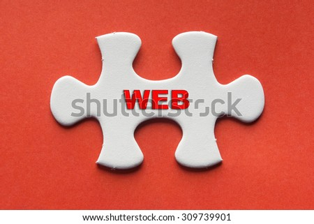 White jigsaw puzzle with a written word web on a red background. - stock photo