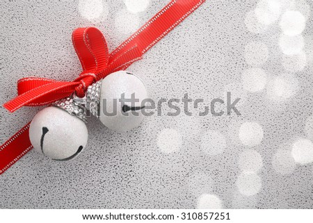 White jingle bell with ribbon bow on festive background - stock photo