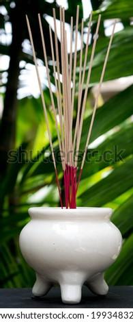 white joss stick pot in a garden - stock photo
