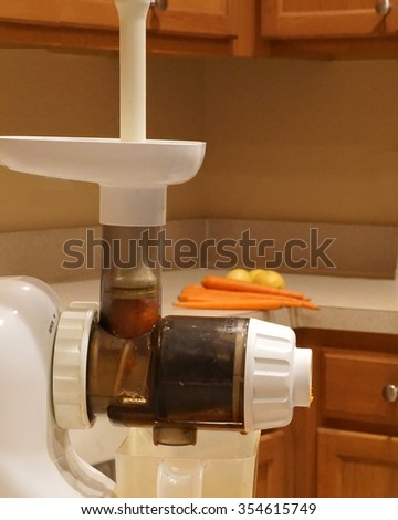 White juicer and carrots/Food Grinder /  Vegetables are being prepared for enjoyment