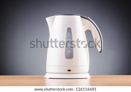 White kettle against grey background - stock photo