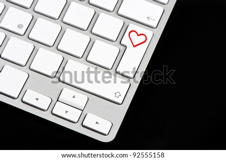 white keyboard with red heart button on black background