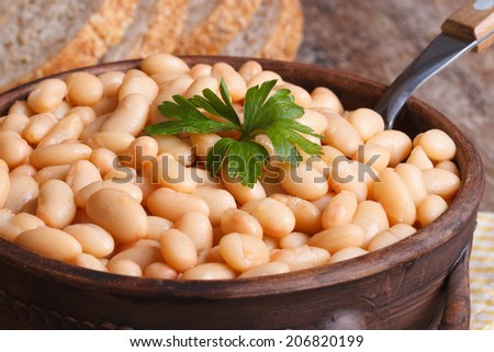 white kidney beans in a brown pot macro and bread on the table horizontal   - stock photo