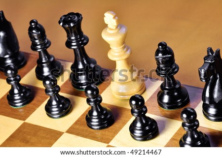 White king among black pieces. Shallow dof. - stock photo