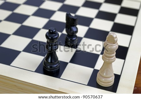 white king under checkmate done by black queen and knight