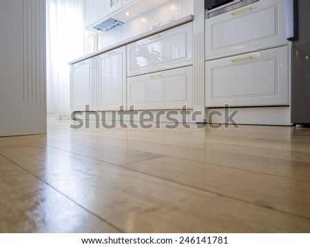 White kitchen and parquet floor - stock photo