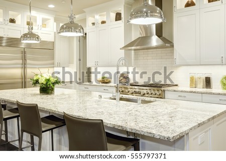 white kitchen design features large bar style kitchen island with granite countertop illuminated by modern pendant - Granite Kitchen Countertops Pictures