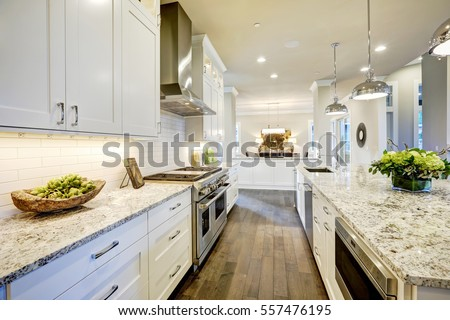 White Kitchen Design Features Large Bar Style Kitchen Island With Granite  Countertop Illuminated By Modern Pendant