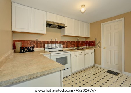 White kitchen room with tile floor and brown back splash tile. House interior.