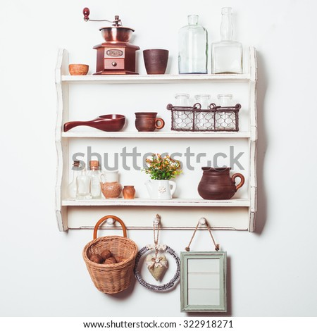 White kitchen shelves in rustic style with kitchenware on the white wall