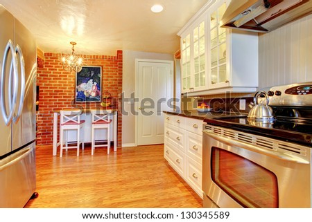 White kitchen with brick wall, hardwood and stainless steal stove and fridge. - stock photo