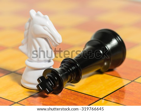 White knight chess piece and fallen black king on chess board -Strategy, competition and leadership concept. - stock photo
