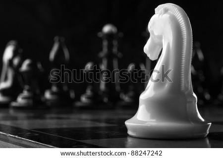 white knight chess piece on the board background - stock photo