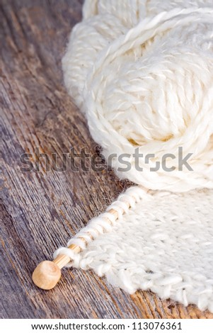White knitting and wooden needles on rustic background - stock photo